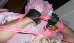 Hands tied up and cuffed above AB Lucinda's head on the nappy changing table.